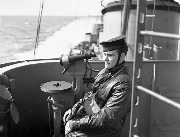 Unidentified sailor on watch aboard H.M.C.S. IROQUOIS at sea, 1943.