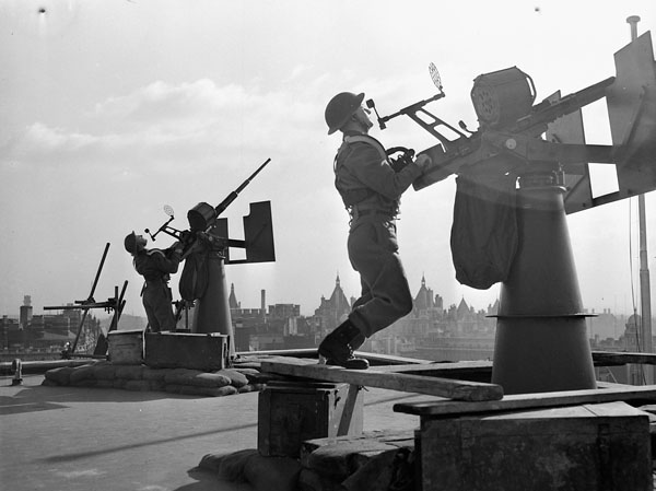 Anti-aircraft gunners manning their guns on the roof of Canadian Military Headquarters, London, England, November 1942.