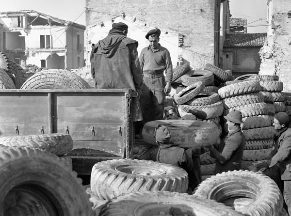 Loading used rubber tires being returned to England for recycling, 5th Canadian Armoured Division Ordnance Field Park, Royal Canadian Ordnance Corps, Rimini, Italy, 22 January 1945.