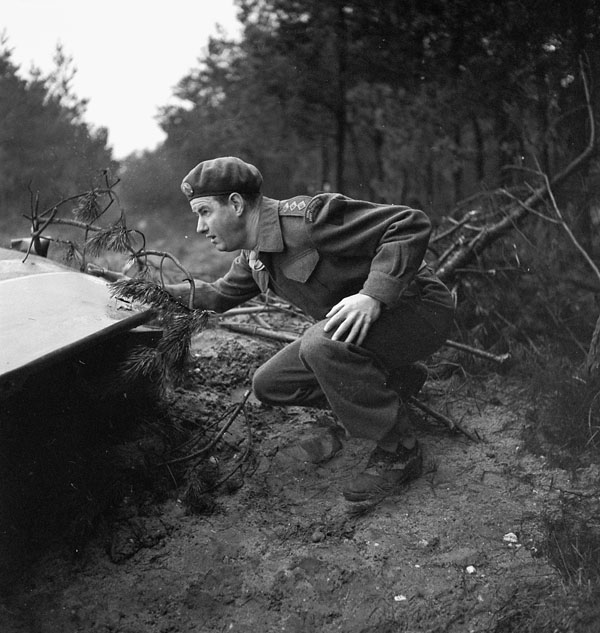 Captain B.D. Graham crouches by a glider as he tries to find out the source of German mortar fire, Nijmegen, Netherlands, 8 February 1945.