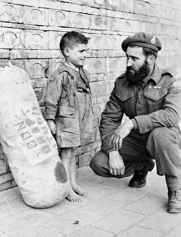 Private J.S.P. Bowen, Princess Patricia's Canadian Light Infantry (P.P.C.L.I.), saying goodbye to a young friend before leaving Italy for a thirty-day Christmas leave in Canada. Italy, 1944.