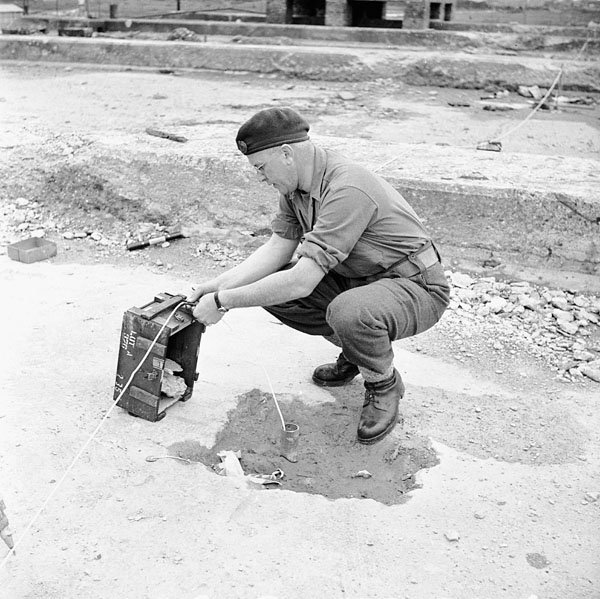 Lieutenant L.E. Labow, 2nd Drilling Company, Royal Canadian Engineers (R.C.E.), checking the fuse of the charge which will demolish former German E-Boat pens, Ostend, Belgium, 21 May 1945.