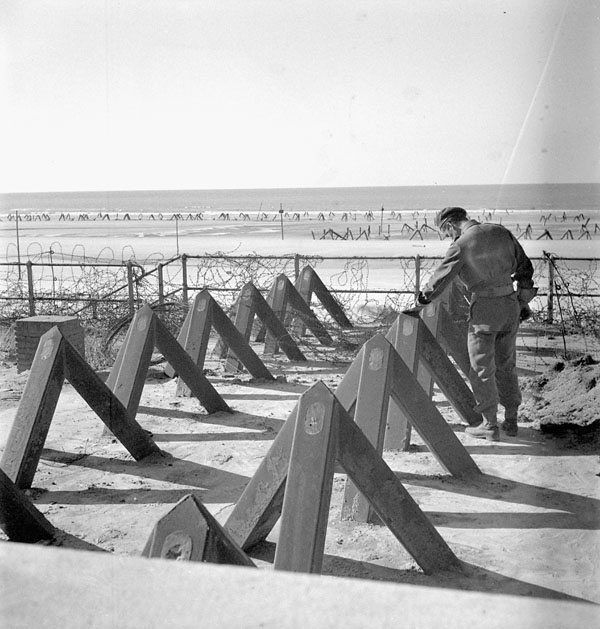 Unidentified Canadian soldier examining German-installed tank obstacles on the beach at Blankenberghe, Belgium, 11 September 1944.