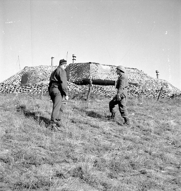 Captain Kingston and Lance-Corporal E.R. Volpe of the 4th Canadian Infantry Brigade examining a camouflaged German command post north of Nieuport, Belgium, 13 September 1944.