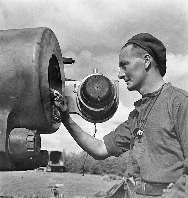 Gunner M. Lupton of the 6th Field Regiment, Royal Canadian Artillery (R.C.A.), cleaning the breach of a French 155mm coastal gun which had been used by a German coastal artillery unit north of Nieuport, Belgium, 13 September 1944.