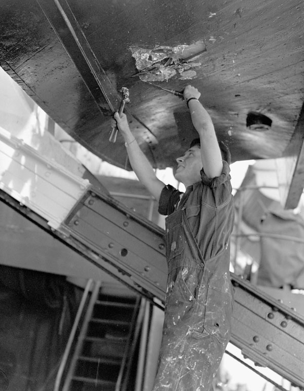 Petty Officer Shipwright R. Abernethy repairing mine damage to one of the Landing Craft Assault (LCA) of H.M.C.S. PRINCE HENRY on D-Day, France, 6 June 1944.