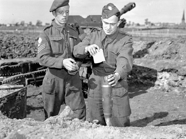 Private R.J. Travis of No.3 Leaflet Unit placing propaganda leaflets into a shell to be fired by Sergeant T. McCormick of the 191 Hearst and Essex Yeomanry Field Regiment, Royal Artillery (R.A.) (British Army), into German-held positions in Dunkirk, France, ca. 15-25 September 1944.