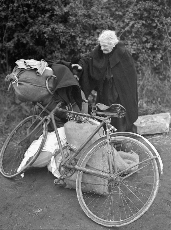 An elderly woman with a bicycle pauses for a rest after being evacuated from Dunkirk during a 36-hour truce arranged by British and German troops. Esquelbec, France, 6 October 1944.