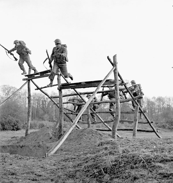 Infantrymen of the Cape Breton Highlanders running through the obstacles of an assault course, Sheffield Park, England, 8 December 1942.