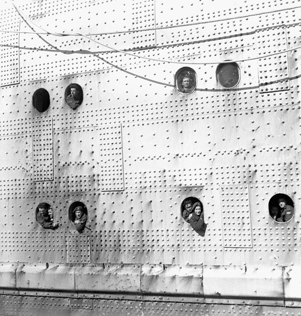 Canadian soldiers leaning out of the portholes as H.M.T. QUEEN ELIZABETH arrives in New York, N.Y., 2 February 1946.