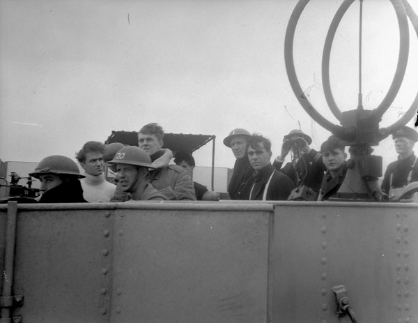 Officers and ratings on the bridge of the destroyer H.M.C.S. RESTIGOUCHE watching a torpedoed Greek merchant ship at sea, ca. 1941.