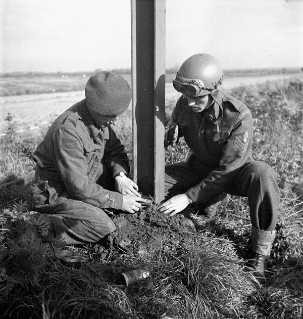 Sapper S. Tomlinson and Sergeant N. Loiselle, 2nd Field Company, Royal Canadian Engineers (R.C.E.), placing a charge to topple a tramcar pole being salvaged for its steel, Ossendrecht, Netherlands, 21 October 1944.