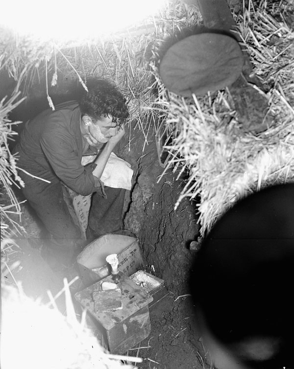 Private E.A. Shirreff uses a  former German trench as a shelter to shave and clean up, Zuid-Beveland, Netherlands, 1 November 1944.