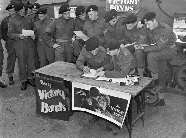 Troopers at No.2 Canadian Armoured Corps Reinforcement Unit (C.A.C.R.U.) buying bonds during the Fifth Victory Loan campaign, England, 13 October 1943.