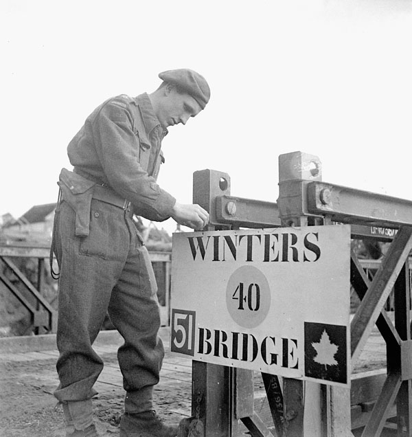 Lieutenant W.A. Bowman placing a sign naming Winters Bridge, a temporary bridge across the Antwerp Canal named in memory of the late Lance-Corporal Winters of the 11th Field Squadron, Royal Canadian Engineers (R.C.E.), Lochtenberg, Belgium, 4 October 1944.