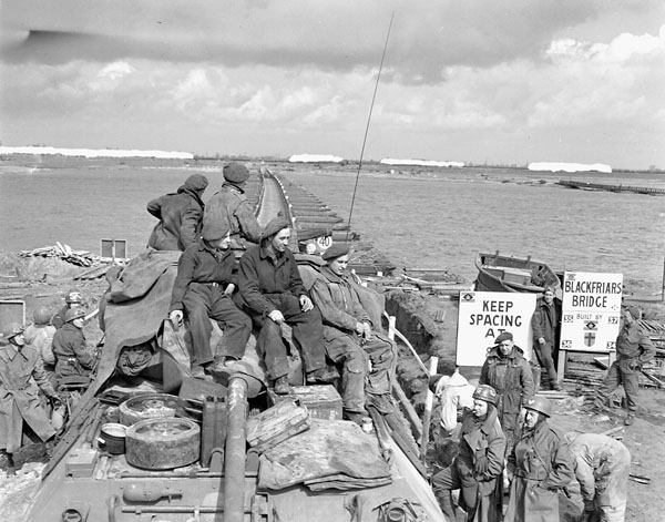 Sappers of the 29th Field Company, 30th Field Company, and 31st Field Company, Royal Canadian Engineers (R.C.E.), prepare to cross Blackfriars Bridge over the Rhine River, Rees, Germany, 30 March 1945.