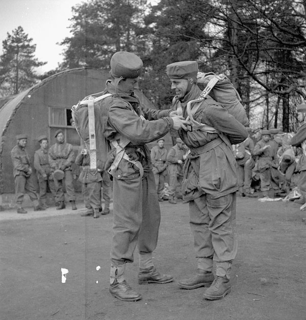 Major the Honourable H. Fraser (left) adjusting the parachute harness of Lieutenant R.C. Hilborn of the 1st Canadian Parachute Battalion before he makes a static balloon jump at the Royal Air Force Parachute Training School, Ringway, Cheshire, England, 4 April 1944.