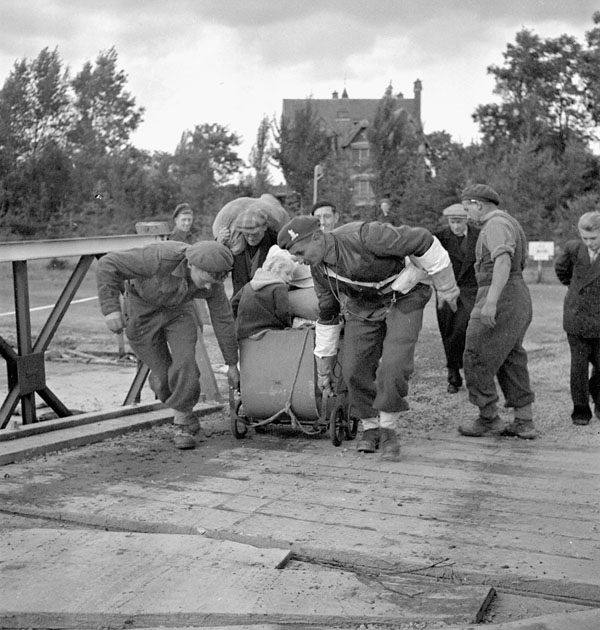 Lance-Corporal A.A. Shaylor of No.2 Provost Company, Canadian Provost Corps, and members of the Royal Canadian Engineers (R.C.E.) assisting Belgian refugees to cross a Bailey Bridge over the Albert Canal, Belgium, 28 September 1944.