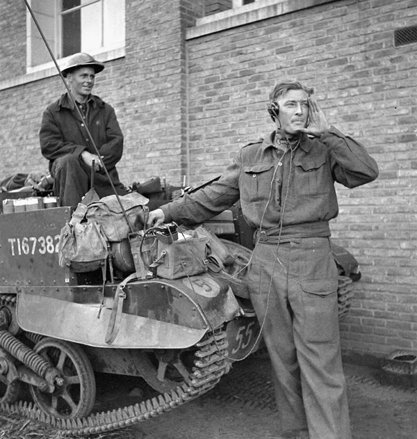 Corporal W.E. Oliver, Royal Regiment of Canada, directing mortar fire, watched by Private J. Keller, driver of their Universal Carrier, France, 28 September 1944.