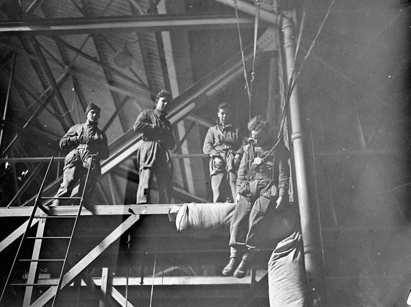 Paratrooper trainees of the 1st Canadian Parachute Battalion in a high swing, a training apparatus devised to teach trainees how to control their parachutes during descent and landing, Royal Air Force Parachute Training School, Ringway, Cheshire, England, 4 April 1944.