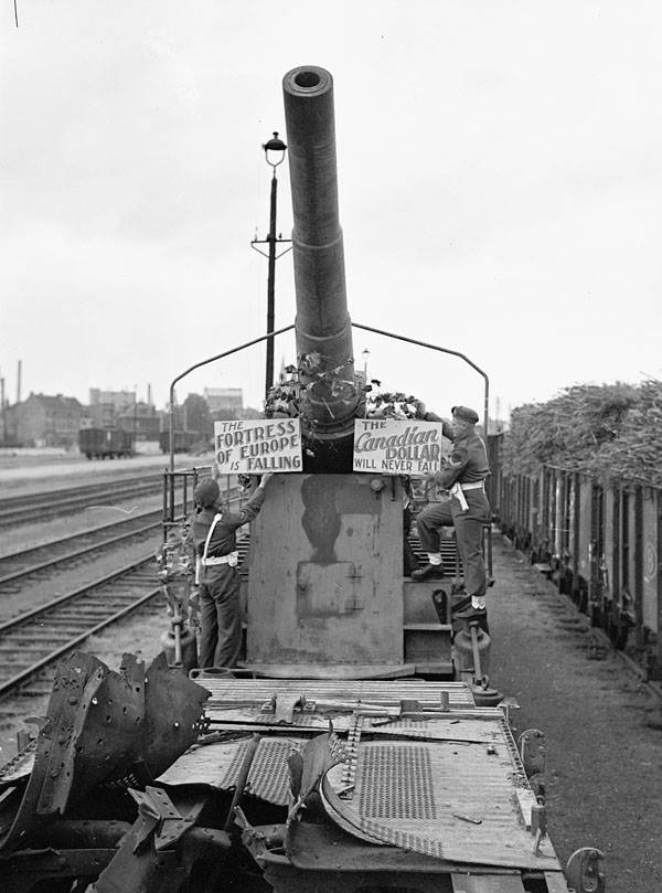 Lance-Corporal Eddie Gallant and Corporal H.E. Popkey hanging 7th Victory Loan Campaign signs on a German railway gun captured by the 4th Canadian Armoured Division during fighting along the Leopold Canal, Eecloo, Belgium, 13 October 1944.
