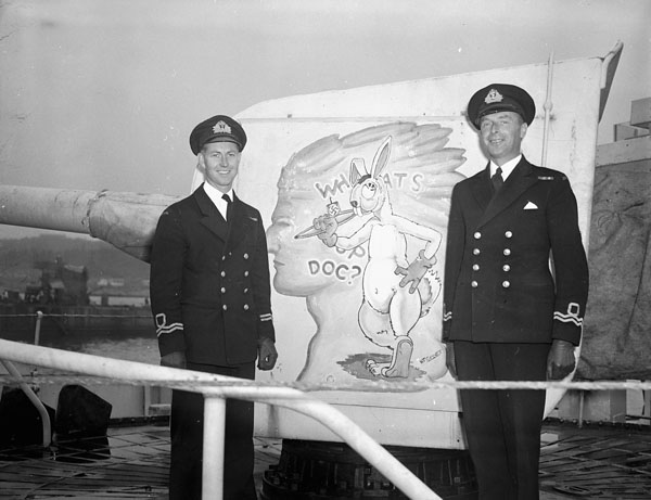 Two officers of H.M.C.S. CHICOUTIMI standing by the gunshield art of the ship's forward gun, Halifax, Nova Scotia, Canada, June 1945.