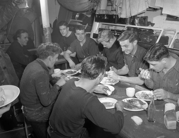 Unidentified crewmen of the minesweeper H.M.C.S. STRATFORD having a meal in their messdeck, St. John's, Newfoundland, November 1943.