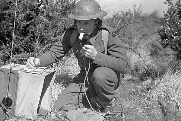Unidentified signalman of The Saskatoon Light Infantry (M.G.) noting a message during a training exercise, Winston Park, England, 15 April 1942.