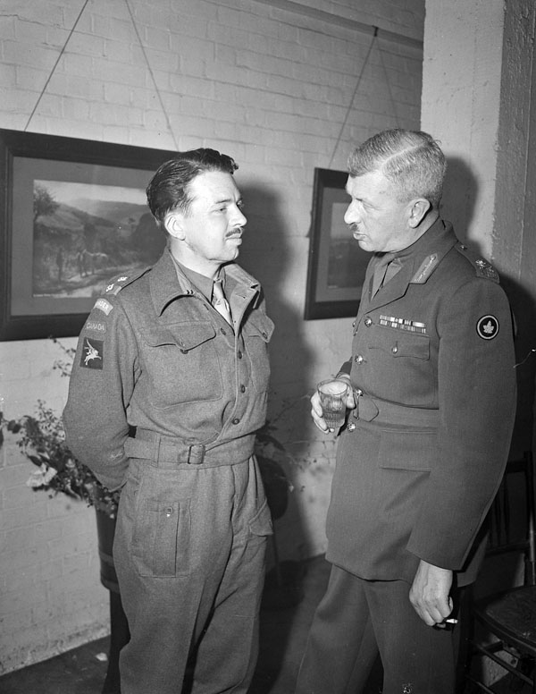 Lieutenant G.P. Comper (left), a paratroop officer who fought at Arnhem, talking with Major-General E.G. Weeks at the first annual reunion of CANLOAN officers, Royal Empire Society, London, England, 14 April 1945.