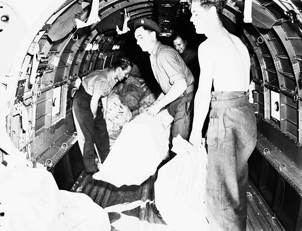 Personnel unloading mail from a Douglas Dakota III aircraft of No.437(Husky) Squadron, R.C.A.F., Teuge, Netherlands, 21 June 1945.