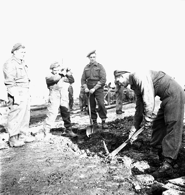 Personnel of the 3rd Battalion, Royal Canadian Engineers (R.C.E.), excavating the route of an Ostend-Ghent oil pipeline, Ostend, Belgium, 18 October 1944.