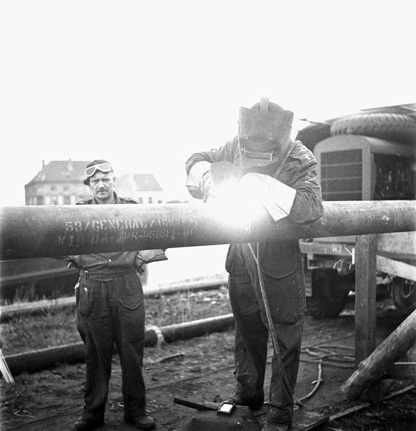 Personnel of the 3rd Battalion, Royal Canadian Engineers (R.C.E.), welding a section of the Ostend-Ghent oil pipeline, Ostend, Belgium, 18 October 1944.