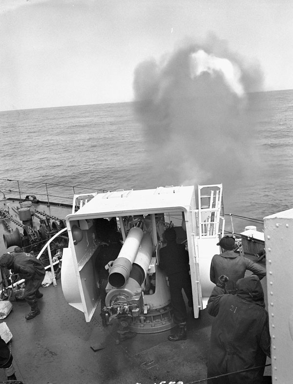 Personnel firing the four-inch gun of the corvette H.M.C.S. SHERBROOKE at sea, June 1945.