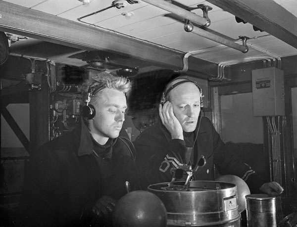 R. Cosburn and Lieutenant F.A. Beck (right) at the Asdic set on the bridge of H.M.C.S. BATTLEFORD, Sydney, Nova Scotia, Canada, November 1941.