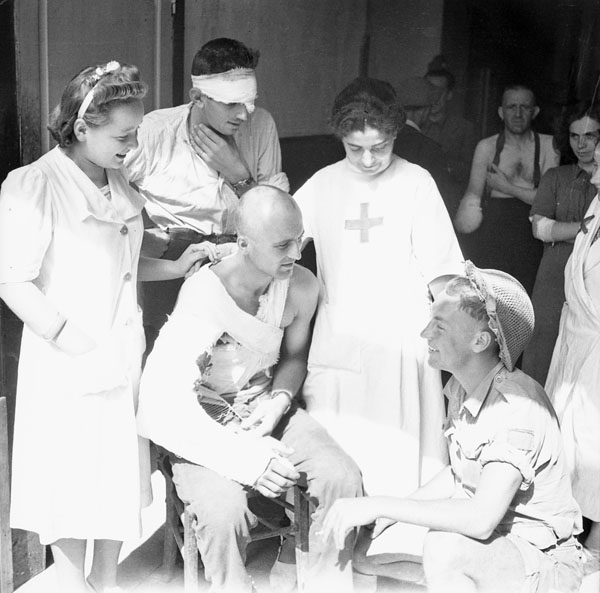 Private R.E. Pavely (lower right) of the 2nd Canadian Infantry Brigade talking with nurses and patients at a hospital in Avigliano, Italy, ca. 21-22 September 1943.
