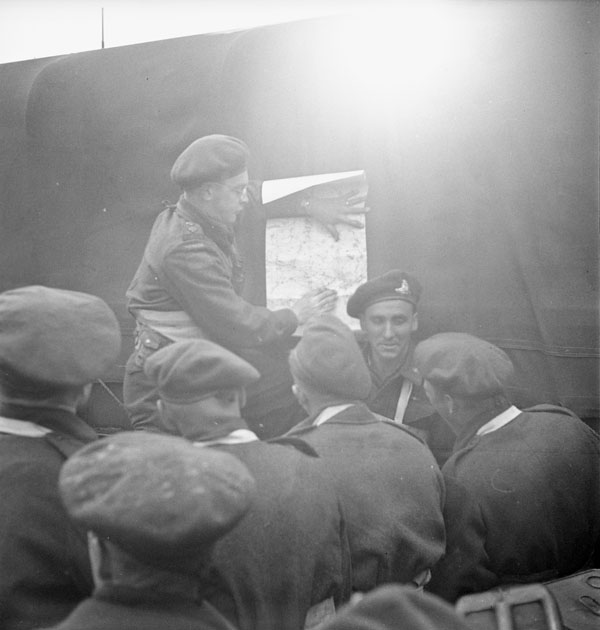 Lieutenant W. Lee briefing infantrymen of the Highland Light Infantry of Canada aboard a Landing Ship Tank en route to France, 3 June 1944.