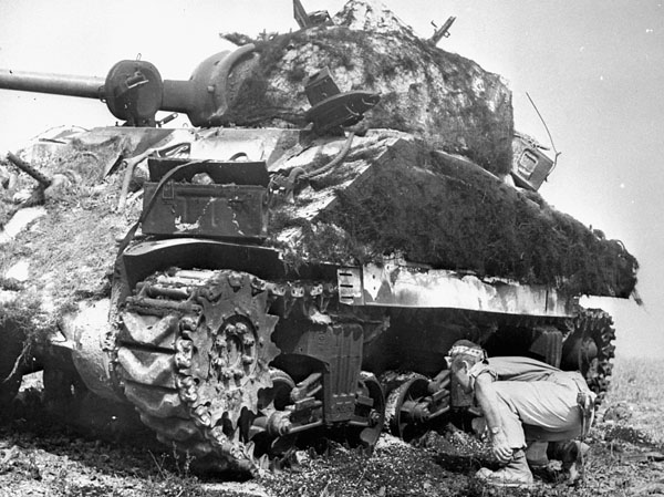 Unidentified infantryman, possibly of the Cape Breton Highlanders, examining the treads of a Sherman tank, possibly of