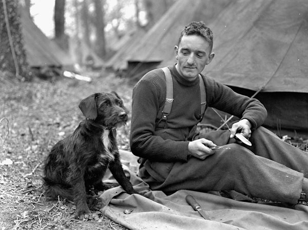 An unidentified member of the Sherbrooke Fusiliers Regiment with his unit's canine mascot, England, 20 April 1944.