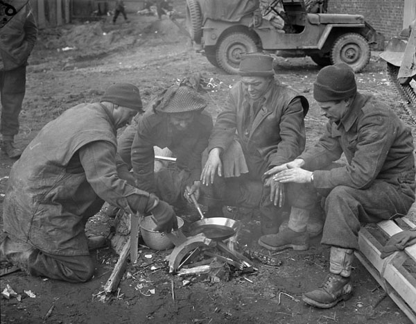 Infantrymen of The Argyll and Sutherland Highlanders of Canada cooking a meal and warming themselves around a fire in a barnyard near Veen, Germany.