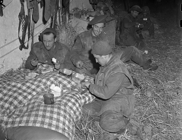 Infantrymen of the Argyll and Sutherland Highlanders of Canada having dinner in a barn near Veen, Germany, 7 March 1945.