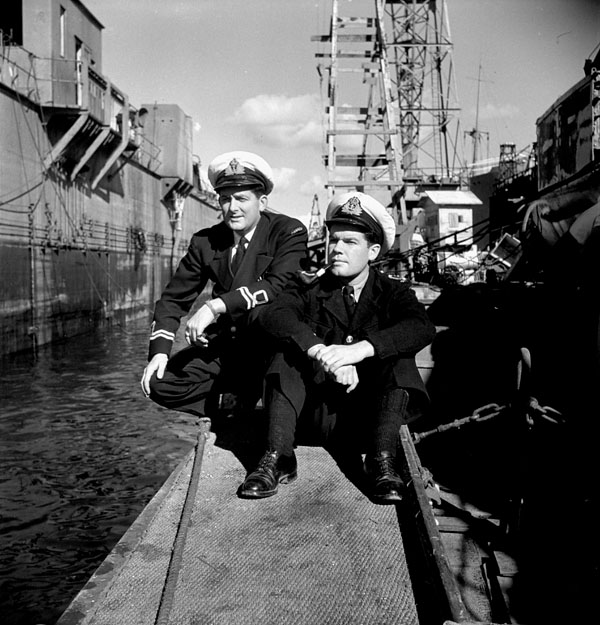 Information officers Lieutenants Gilbert A. Milne (left) and Scott Young, both of H.M.C.S. PRINCE HENRY, in a drydock, Taranto, Italy, October 1944.