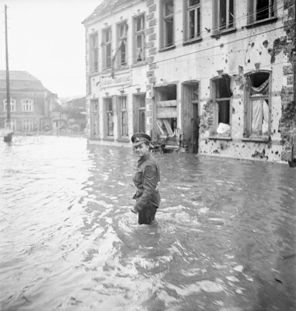 An unidentified member of the Canadian Provost Corps on a flooded street, Kranenburg, Germany, 13 February 1945.