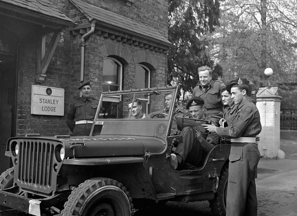 Private Maurice Richard (right), Canadian Provost Corps, talking with students of the Khaki University of Canada, who ride in a jeep driven by Lance-Bombardier R.S. Hughes, Leavesden, England, 15 April 1946.