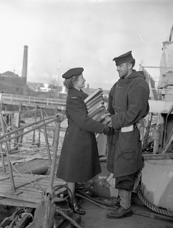 Leading Wren Ruth Church, Women's Royal Canadian Naval Service (W.R.C.N.S.) delivering a supply of library books to Able Seaman Bill Swetman of H.M.C.S. PETROLIA, Londonderry, Northern Ireland, November 1944.