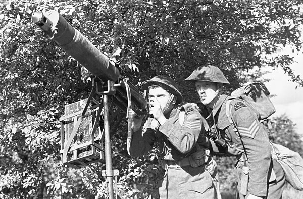 Unidentified sergeants of the Saskatoon Light Infantry (M.G.) firing a machine gun during a training exercise, Wandsworth, England, 1 October 1942.