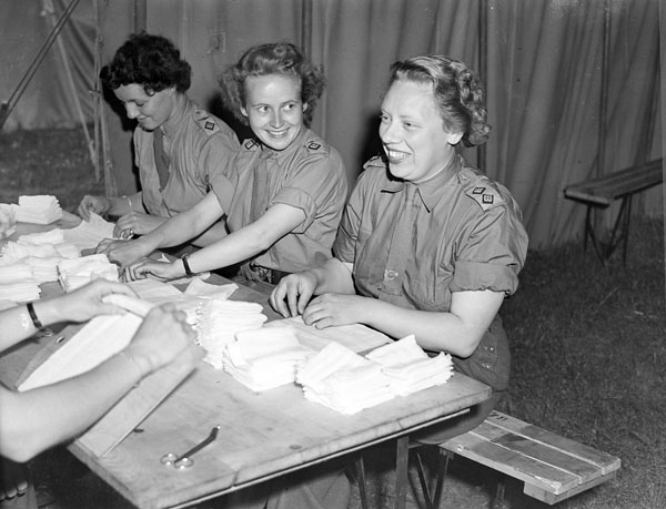 Nursing sisters of the Royal Canadian Army Medical Corps (R.C.A.M.C.) making bandages at a British hospital in the Normandy bridgehead, France, 17 July 1944.