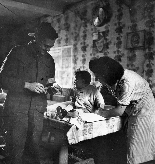Captain Earl Bourbonnais, 23rd Field Ambulance, Royal Canadian Army Medical Corps, inoculating Nicole Pierre, Basly, France, ca. 27-28 June 1944.