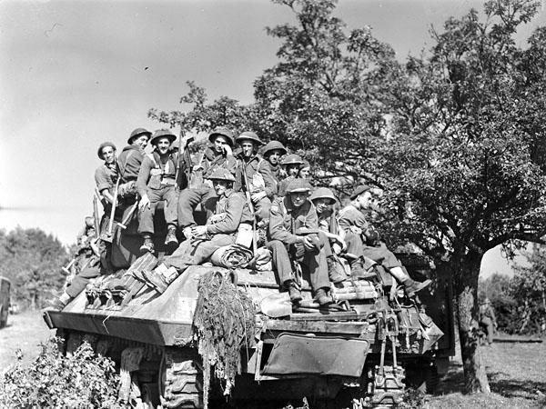 Infantrymen of Le Régiment de la Chaudière riding on an M-10 A1 tank destroyer vehicle of the 3rd Anti-Tank Regiment, Royal Canadian Artillery (R.C.A.) during the attack on Elbeuf, France, 26 August 1944.