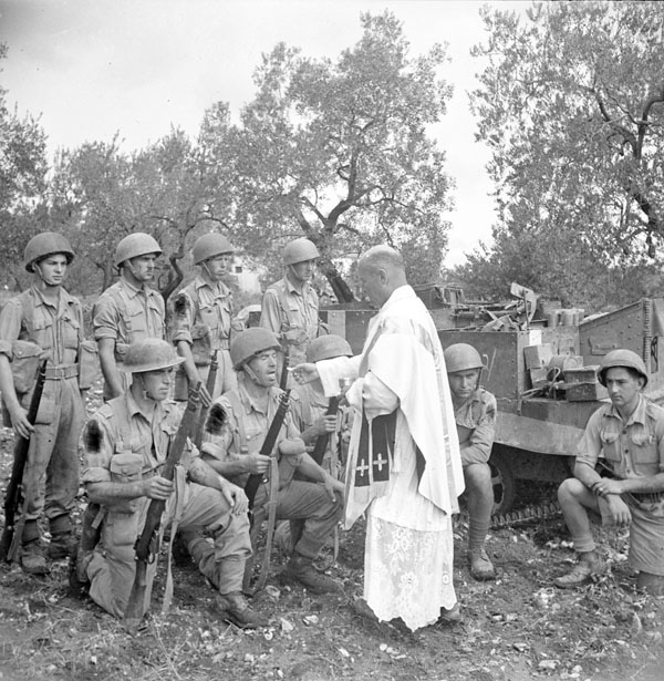 Infantrymen of the Royal 22e Régiment receiving Holy Communion from the unit's chaplain, H/Major Leo Grattan, before going on a reconnaissance patrol, Italy, October 1943.