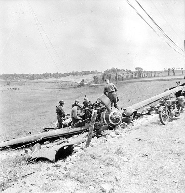 Canadian soldiers draining gasoline from a damaged Messserschmidt 109 aircraft that crash-landed beside a German radar station near Beny-sur-Mer, France, 16 June 1944.